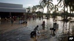 Warga berupaya mencari barang-barang berharga di areal parkir di sekitar toko, selatan Acapulco, di Punta Diamante, Meksiko, melalui air banjir yang masih setinggi pinggang, Rabu (18/9).