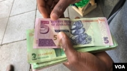 FILE: A man in Harare holds bondnotes issued by Reserve Bank of Zimbabwe, Oct. 15, 2018. The introduction of bond notes - a currency Zimbabwe started printing two years ago to ease the situation -- has not helped. (C.Mavhunga/VOA)