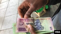 FILE: A man in Harare holds bondnotes issued by Reserve Bank of Zimbabwe, Oct. 15, 2018. The introduction of bond notes - a currency Zimbabwe started printing three years ago to ease the situation -- has not helped. (C.Mavhunga/VOA)
