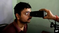 In this May 16, 2012 file photo, an Indian man gets his retina scanned as he enrolls for Aadhar, India's biometric \ID project in Kolkata, India. (AP Photo/Bikas Das, File)