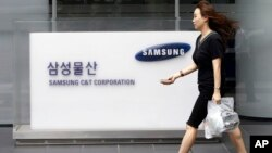 An office worker walks by a logo of Samsung C&T Corp., at its head office in Seoul, South Korea, Friday, July 17, 2015.