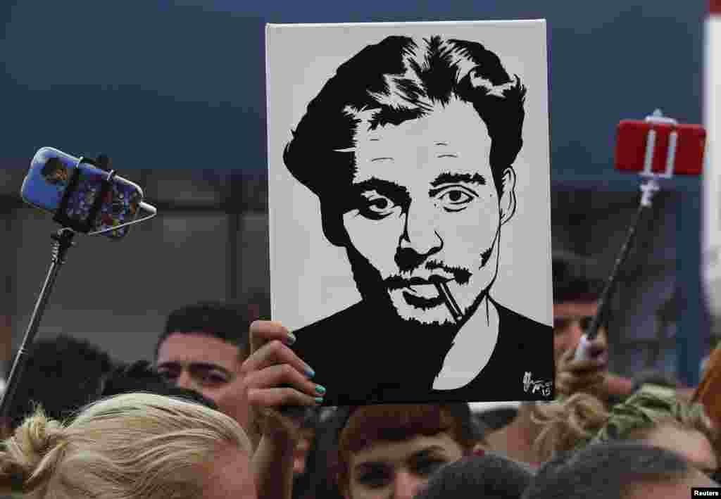 """Một cô gái cầm một bức chân dung của nam diễn viên Johnny Depp trước lối vào địa điểm tổ chức Liên hoan Phim Venice lần thứ 72 ở miền bắc nước Ý. Depp tham dự sự kiện thảm đỏ cho bộ phim """"Black Mass."""""""