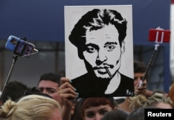 A girl (C) holds up a portrait of actor Johnny Depp in front of the entrance of the venue of the 72nd Venice Film Festival, Sept. 4, 2015.