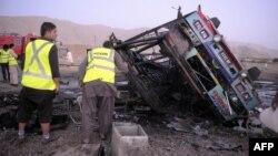 Pakistani volunteers search for blast victims in the wreckage of a destroyed passenger bus following a bomb explosion in Mastung district, about 25 kilometres south of Quetta, the capital of insurgency-hit Baluchistan province, September 18, 2012.