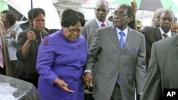 FILE: Zimbabwean President Robert Mugabe (R) is greeted by Vice President Joice Mujuru (L) after a trip to Singapore, April 12, 2012.