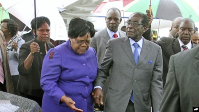 Zimbabwean President Robert Mugabe (R) is greeted by Vice President Joice Mujuru (L) after a trip to Singapore that had ignited speculation the veteran leader was seriously ill, as he returns home to Harare, Zimbabwe, April 12, 2012.