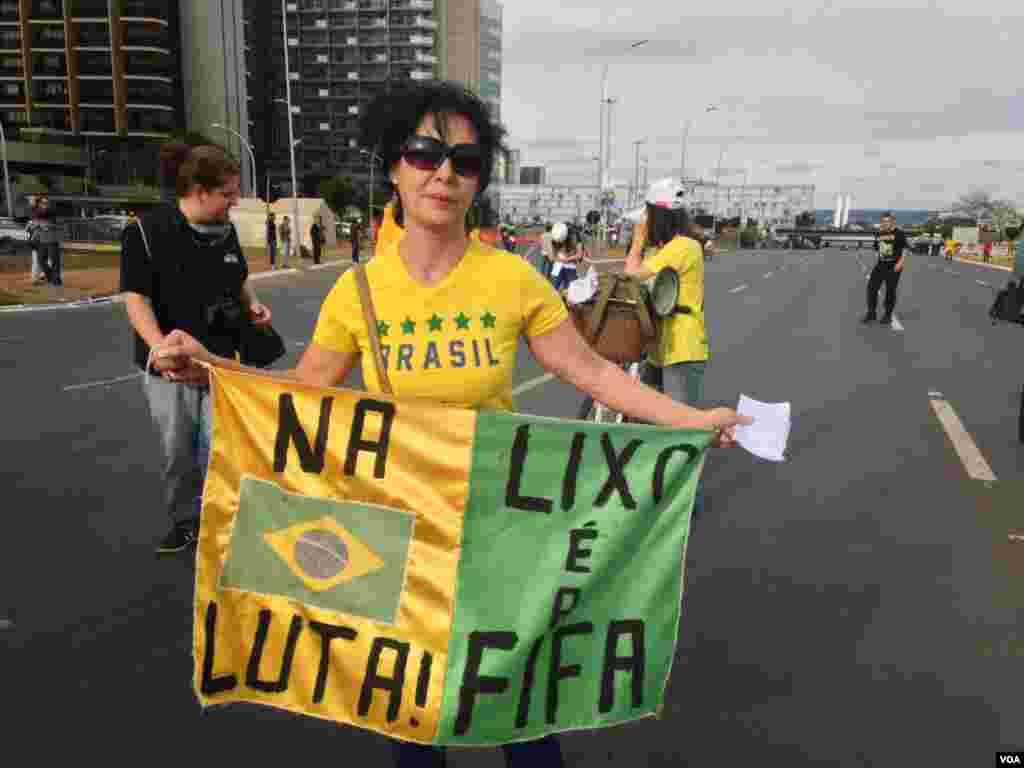 """A protester holds a banner that reads in Portuguese """"Fight, FIFA is Trash"""" during a World Cup protest in Brasilia, Brazil, June 23, 2014. (Nicolas Pinault/VOA)"""