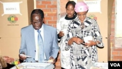 President Robert Mugabe voting in Harare's Highfield suburb Wednesday with his wife, Grace, and daughter Bona