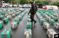 FILE - A police officer guards packages of seized marijuana on display for a media presentation at police headquarters in Cali, Colombia, March 26, 2013. According to police, the 7.7 tons of marijuana were seized from the rebels of the Revolutionary Armed Forces of Colombia, FARC, during a raid in a highway near Cali.