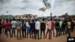 Les manifestants chantent l'hymne national congolais autour d'un rond-point à Beni lors d'une manifestation contre le report des élections sur le territoire des Beni et de la ville de Butembo le 27 décembre 2018.