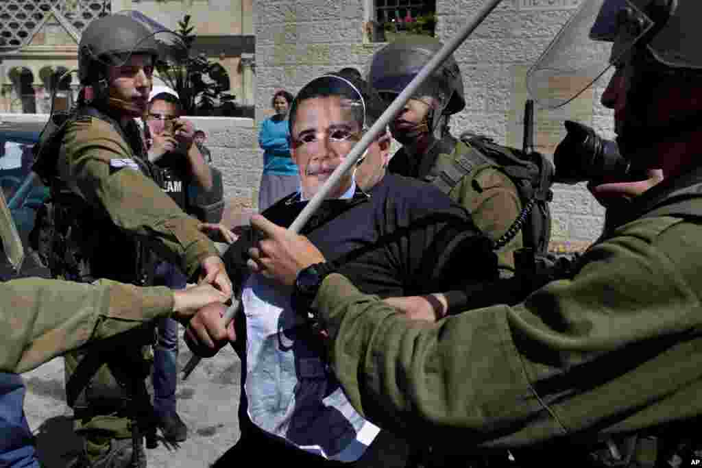 Israeli soldiers scuffle with a Palestinian activist wearing a mask of U.S. President Barack Obama during a protest in the West Bank town of Hebron, March 20, 2013.