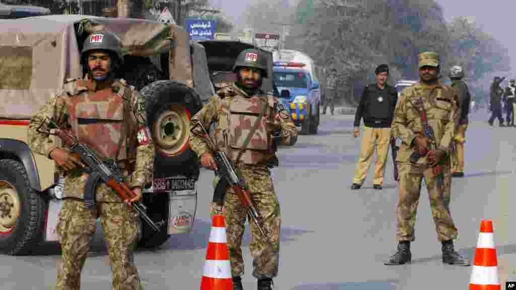 Pakistani army troops cordon off a road leading to a school under attack by Taliban gunmen in Peshawar, Pakistan, Dec. 16, 2014.