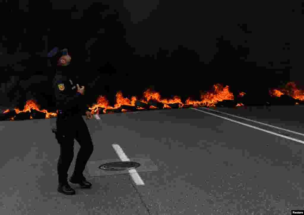 A member of riot police walks in front of a flaming barricade during a May Day rally in Gijon, Spain.
