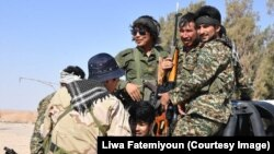 FILE - Afghan fighters with the Fatimiyoun Brigade in Syria.