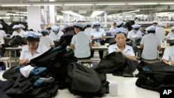 FILE - North Korean workers assemble Western-style suits on Sept. 21, 2012, at the South Korean-run ShinWon Corp. garment factory inside the Kaesong industrial complex in Kaesong, North Korea.