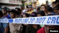 FILE - People stand behind a police line at a crime scene in Tegucigalpa, Honduras, Nov. 19, 2013.