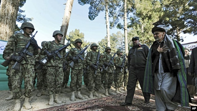 Ashraf Ghani Ahmadzai (R), head of the Transition Commission, inspects an Afghan military guard during a ceremony to hand over security control in Qala Naw, center of Badghis province, File January 31, 2012.