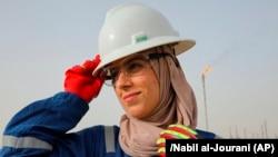 Zainab Amjad, a petrochemical engineer, poses for a photo near an oil field outside Basra, Iraq, Monday, February 18, 2021. (AP Photo/Nabil al-Jourani)