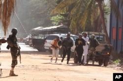 People run to flee from the Radisson Blu Hotel in Bamako, Mali, Nov. 20, 2015.