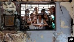 Para narapidana mengamati suasana luar dari jendela kantor penjara Tanjung Gusta yang terbakar, Jumat (12/7).