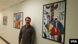 직장 복도에 걸어놓은 자신의 미술 작품들 앞에 선 루크만 아흐마드.