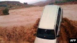 A car is carried away by flood waters in the southern region of Ouarzazate in Morocco, Nov. 22, 2014.