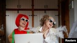 """Emily berdandan seperti Elton John dan Molly sebagai Lady Gaga menyaksikan konser """"One World: Together at Home"""" dari rumah mereka di Henton, Inggris, di tengah pandemi virus corona (Covid-19), Sabtu, 18 April 2020. (Foto: Reuters)"""