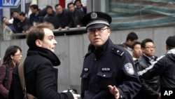 "Policeman asks foreign journalist to leave area near Peace Cinema, after calls for a ""Jasmine Revolution"" protest, organized through internet, in downtown Shanghai, February 27, 2011"