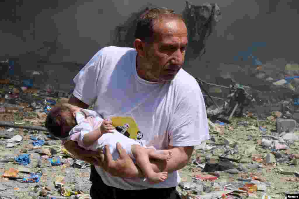 A man holds a baby that survived what activists said was hit by a barrel bomb dropped by forces loyal to Syrian President Bashar al-Assad at the old city of Aleppo.