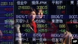 FILE - People are reflected on the electronic board of a securities firm in Tokyo, Japan.