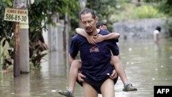 Một người đàn ông Indonesia cõng con trai qua một khu phố bị ngập lụt ở Tangerang trong vùng ngoại ô Jakarta, ngày 27/10/2010