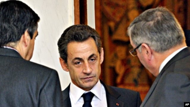 France's President Nicolas Sarkozy speaks with ministers at the end of the weekly cabinet meeting at the Elysee Palace in Paris, February 23, 2011
