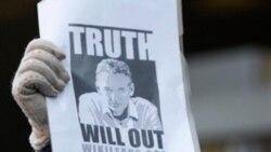 Seorang pendukung Julian Assange mengangkat sebuah poster di depan Pengadilan Westminster di London di mana Assange dibawa ke depan hakim pada tanggal 7 Desember 2010.