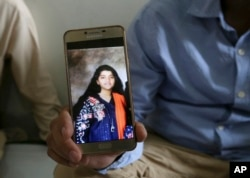 Abdul Aziz Sheikh, father of Sabika Sheikh, a victim of the shooting at a Texas high school, shows a picture of his daughter, in Karachi, Pakistan, May 19, 2018.