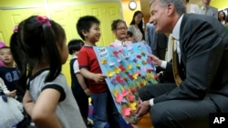Students welcome New York Mayor Bill de Blasio to their pre-kindergarten class at the Brooklyn Chinese American Association Early Childhood Education Center, May 27, 2014, in New York.
