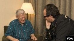 Doc Watson talks to Elvis Costello at MerleFest in 2007 (VOA/Katherine Cole)