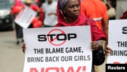 A woman carries a sign as she attends a protest demanding the release of abducted secondary school girls in the remote village of Chibok in Lagos, May 9, 2014.