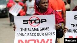 Seorang perempuan memegang plakat bertuliskan seruan untuk pembebasan siswi sekolah yang diculik dari sekolah mereka di Chibok, dalam aksi unjuk rasa di Lagos (9/5).