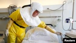 2014年10月15日,瑞士巴塞尔医院的一名感染控制护士穿着防护服向媒体介绍埃博拉病人使用的隔离病房。