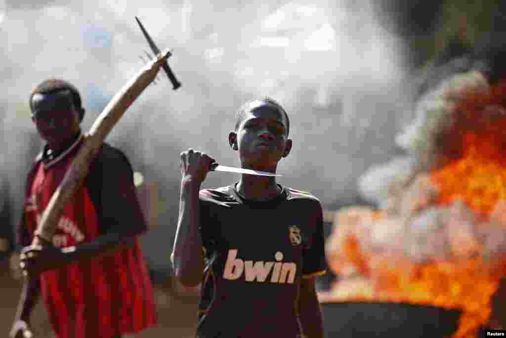A boy gestures with a knife in front of a barricade that is on fire during a protest after French troops opened fire on protesters blocking a road in Bambari, Central African Republic.