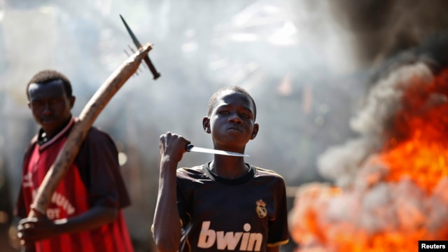 FILE - A boy gestures in front of a barricade on fire during a protest after French troops opened fire at protesters blocking a road in Bambari May 22, 2014.