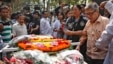 Father Ajay Roy, right, stands beside the coffin of Avijit Roy, a prominent Bangladeshi-American blogger in Dhaka, Bangladesh, March 1, 2015.