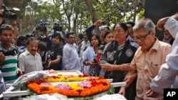 FILE - Father Ajay Roy, right, stands beside the coffin of Avijit Roy, a prominent Bangladeshi-American blogger in Dhaka, Bangladesh, March 1, 2015.