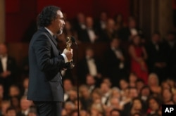 "Alejandro G. Inarritu is seen from backstage as he accepts the award for best director for ""The Revenant"" at the Oscars, Feb. 28, 2016, at the Dolby Theatre in Los Angeles."