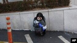 在韩国首尔的一家医院旁,一位粉丝在韩国已故歌手钟铉的葬礼上哭泣。(2017年12月21日)