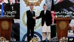Presiden Afghanistan Hamid Karzai berjabat tangan dengan Sekjen NATO Anders Fogh Rasmussen seusai konferensi pers di akademi militer di pinggir ibukota Kabul, Afghanistan (18/6).