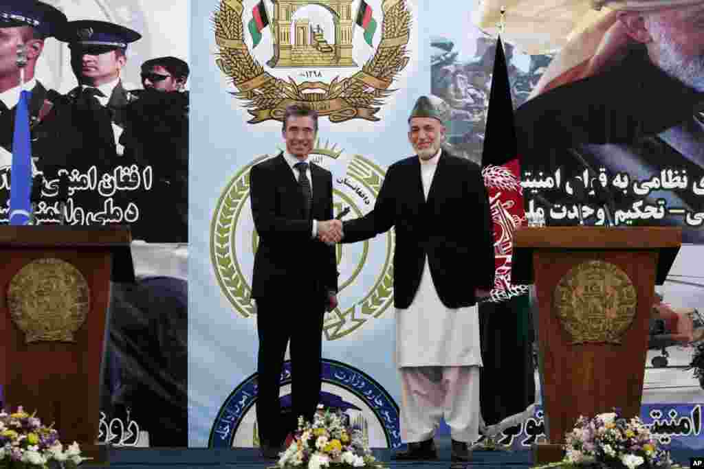 Afghan President Hamid Karzai shakes hands with NATO Secretary-General Anders Fogh Rasmussen after a ceremony at a military academy on the outskirts of Kabul, Tuesday, June 18, 2013.