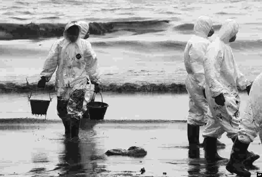 Workers use buckets to remove crude oil during a cleanup operation on the beach of Prao Bay on Samet Island, Thailand, July 30, 2013.