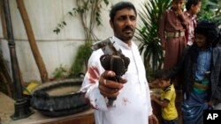 A Houthi Shiite rebel holds part of a projectile launched by Yemeni forces during clashes between Yemeni forces and Houthi militants in Sanaa, Yemen, Sept. 19, 2014.