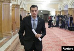 FILE - Romanian Prime Minister Sorin Grindeanu leaves a meeting of the Social Democratic Party at the parliament in Bucharest, Romania, Feb. 6, 2017.